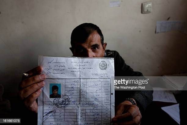 KABUL AFGHANISTAN – JANUARY An employee of the traffic department in Kabul holds the paperwork to renew a driving license Obtaining a vehicle...