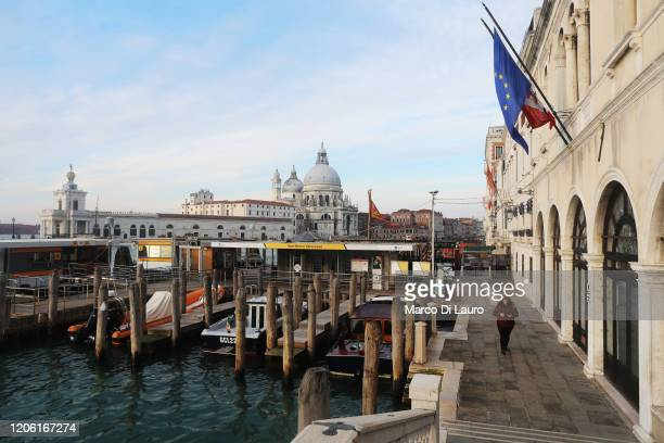 An employee of the Venice municipal transport company walks to her workplace in Piazza San Marco in an empty road on March 9, 2020 in Venice, Italy....