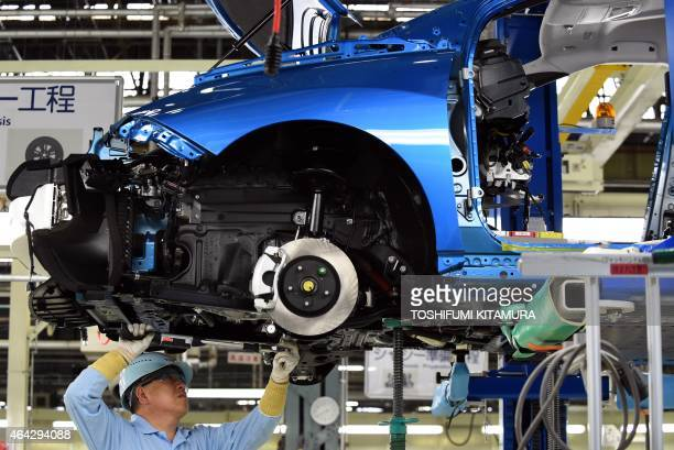 An employee of Toyota Motors assembles FCV Mirai on its assembly line during the vehicle's line off ceremony at the Motomachi factory in Toyota city...
