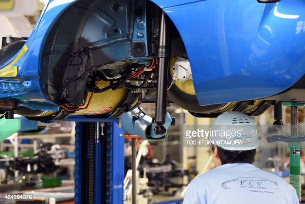 An employee of Toyota Motors checks the hydrogen tanks on the FCV 'Mirai' assembly line during the vehicle's line off ceremony at the Motomachi...