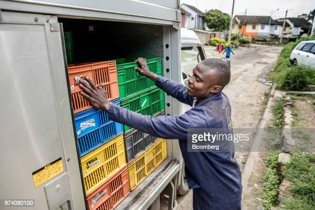 An employee of Twiga Foods Ltd stacks crates in his truck after delivering produce to a stall selling general goods and fresh vegetables in Nairobi...