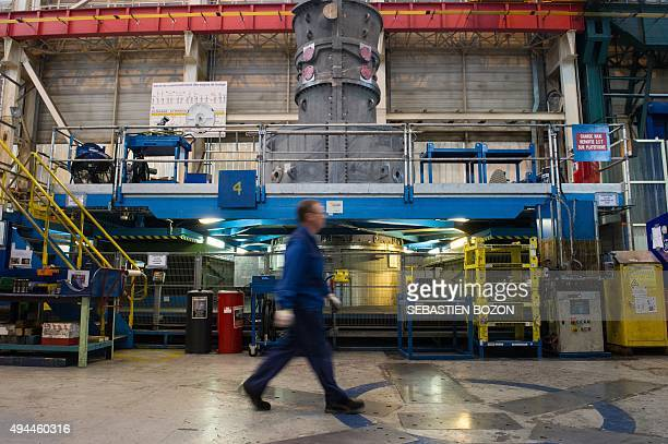 An employee of US multinational General Electric walks past a gas turbine at the GE plant in Belfort eastern France on October 27 2015 AFP PHOTO /...