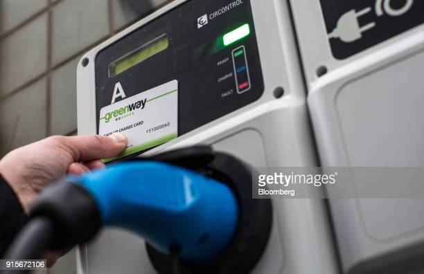 An employee of Voltia uses a backup charge card to start charging a Nissan Voltia env200 electric automobile at a GreenWay Infrastructure sro...