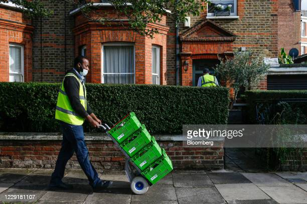 An employee of Waitrose, the grocery store owned by John Lewis Partnership Plc, deliveries groceries in the Maida Vale district of London, U.K., on...
