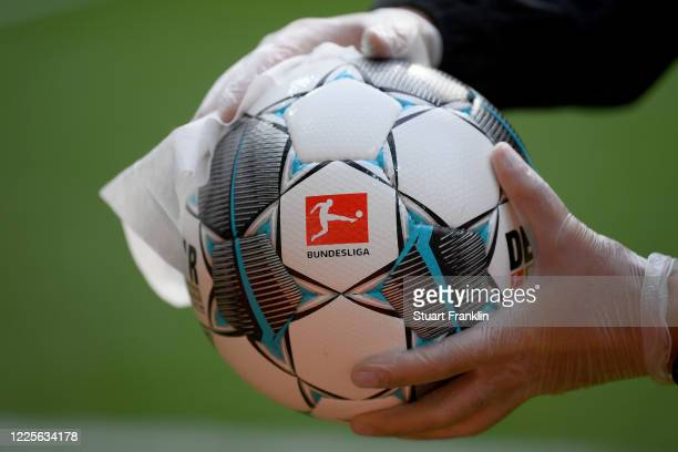 An employee of Werder Bremen disinfects an official match ball ahead of the Bundesliga match between SV Werder Bremen and Bayer 04 Leverkusen at...