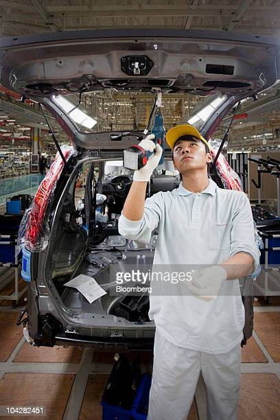 An employee of Zhengzhou Nissan Automobile Co Ltd works on the assembly line of the XTrail sport utility vehicle in Zhengzhou Henan province China on...