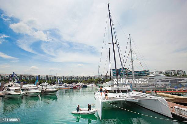 An employee on rigidinflatable boat hose down a catamaran in front of residential buildings in the Sentosa Cove during the Singapore Yacht Show in...