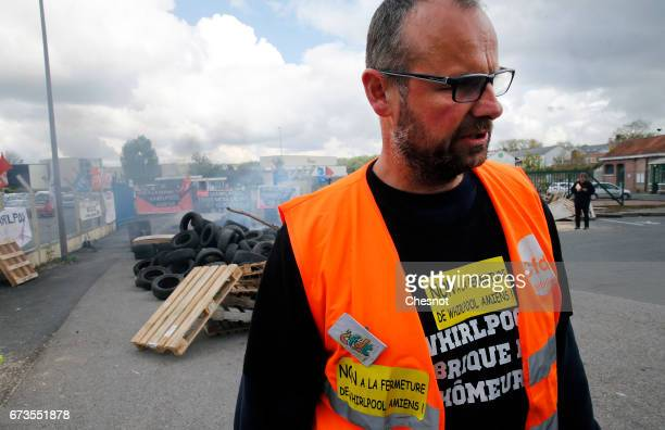 An employee on strike at the Whirlpool factory stands near a barricade to block the entrance ahead of a visit of French presidential election...