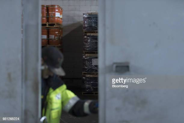 An employee opens a door as barrels of cobalt owned by Cobalt 27 Capital Corp stand stacked beyond in Rotterdam Netherlands on Monday Jan 22 2018...