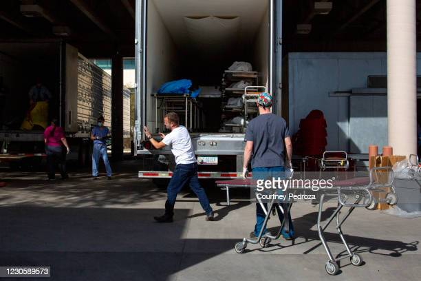 An employee opens the doors to a refrigerated semi-truck containing bodies at the Pima County Office of the Medical Examiner on January 14, 2021 in...