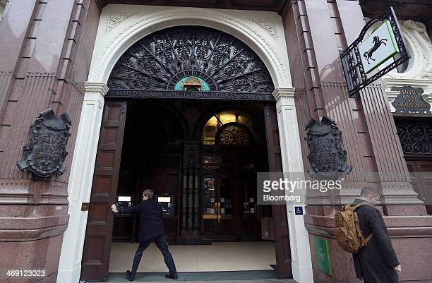 An employee opens the wooden doors of a Lloyds Bank branch a unit of Lloyds Banking Group Plc in London UK on Thursday Feb 13 2014 Lloyds Banking...