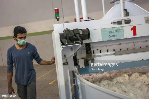 An employee operates a blending machine inside a blowroom unit at the Artistic Denim Mills Ltd factory in Karachi Pakistan on Tuesday Feb 6 2018...