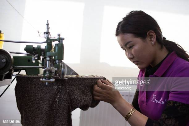 An employee operates a circular knitting machine at a Bodios Co garment factory in Ulaanbaatar Mongolia on Wednesday March 15 2017 Mongolia's gross...