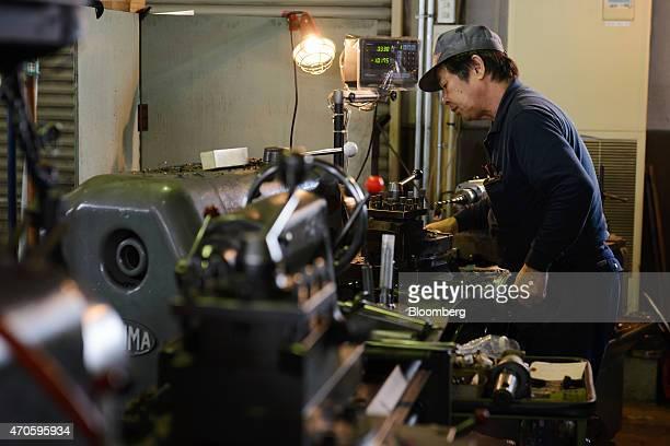 An employee operates a metal lathe at an Osaka Machine Tool Co factory in Higashi Osaka City Osaka Prefecture Japan on Tuesday April 21 2015 At Osaka...
