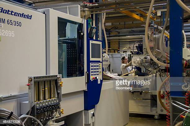 An employee operates a moulding machine in the manufacturing plant at the headquarters of Lego A/S in Billund Denmark on Wednesday Feb 25 2015 Lego...