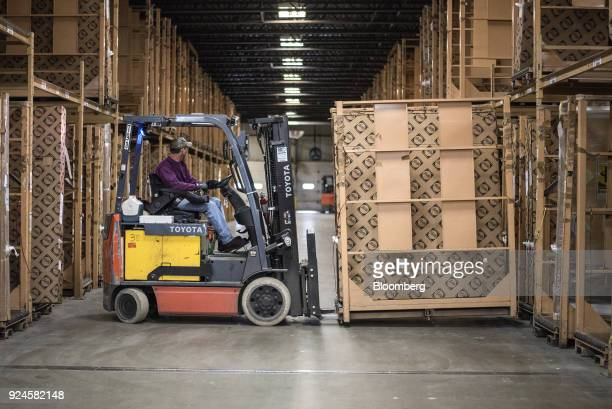 An employee operates a Toyota Material Handling Inc forklift to move a window frame in the storage area of the Pella Corp manufacturing facility in...