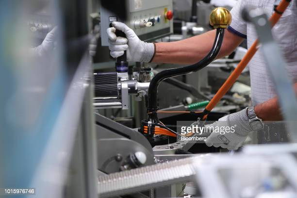 An employee operates machinery on the luxury automobile electromechanical axle roll control device assembly line inside the Schaeffler AG factory in...