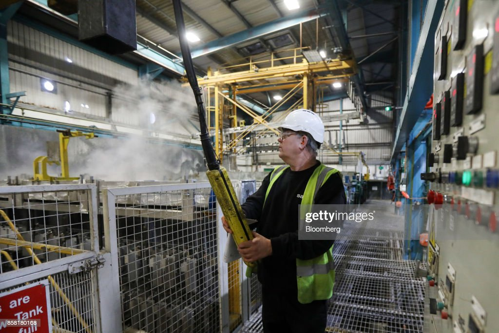 An employee operates machinery to dip aluminum parts into cleaning and anodising tanks at the Sapa SA aluminum plant in Bedwas, U.K., on Wednesday, Oct. 4, 2017. After being closed for three years due to a weak market, Sapa's aluminum plant in south Wales reopened to supply lightweight parts for automakers such as London Electric Vehicle Co., the maker of black cabs. Photographer: Luke MacGregor/Bloomberg via Getty Images