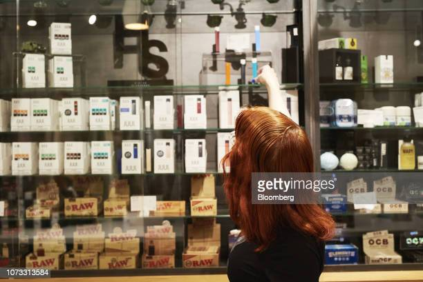 An employee organizes Juul Labs Inc. E-cigarettes displayed for sale at the Higher Standards LLC store in Chelsea Market in New York, U.S., on...