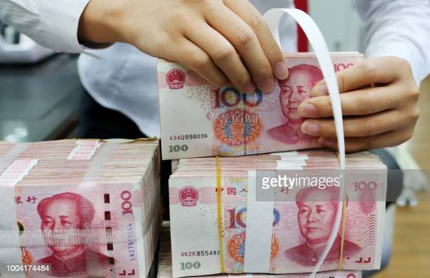 An employee packages 100-yuan notes at a bank in Nantong in China's eastern Jiangsu province on July 23, 2018. - China on July 23 rejected...