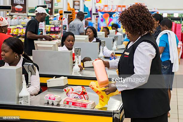 An employee packs a customer's bags with products as cashiers scan goods at the cash desks inside a Shoprite Holdings Ltd supermarket in Alexandra...