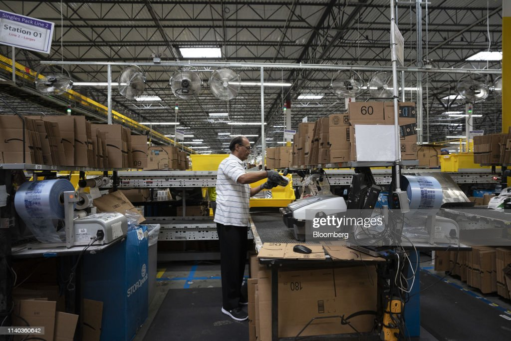 An employee packs orders for shipment at the Amazon com Inc