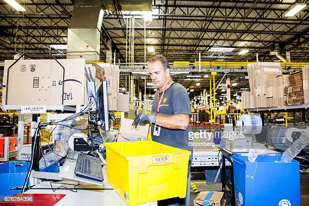 An employee packs orders inside an Amazoncom Inc fulfillment center in Robbinsville New Jersey US on Monday Nov 28 2016 In 2005 retailers coined the...