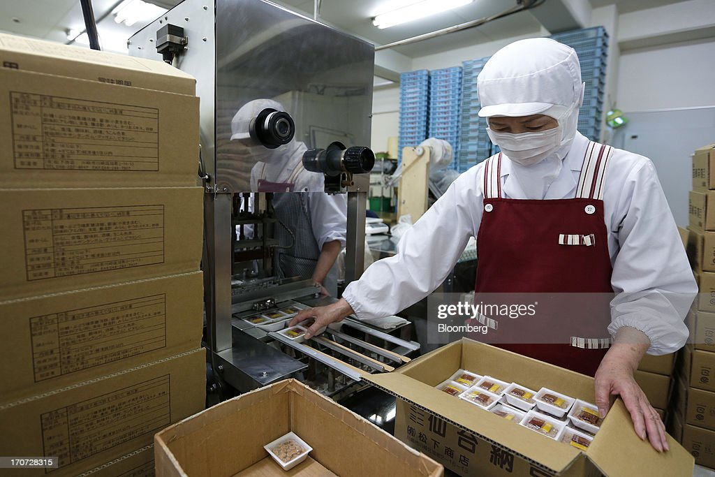 An employee packs sealed polystyrene trays of fermented soybeans, known as natto, into a box at the Matsushita Shoten Y.K. production facility in Kawasaki, Kanagawa Prefecture, Japan, on Friday, June 7, 2013. From Japan's natto makers and operators of neighborhood baths to its largest refiner and utilities, the weaker yen offers domestically focused industries nothing to offset higher import prices. Photographer: Kiyoshi Ota/Bloomberg via Getty Images