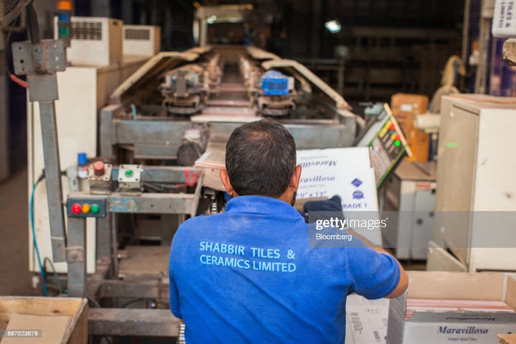 An employee packs tiles from a conveyor into a box at the Shabbir Tiles & Ceramics Ltd. production facility in Karachi, Pakistan, on Wednesday, Dec. 6, 2017. Shabbir, which had suffered four years of losses while fighting to compete with cheap imports from neighboring China, is on course to post an annual profit next financial year after Pakistan placed an anti-dumping duty on Chinese tiles in October. That follows similar moves from the regulator on steel products. Photographer: Asim Hafeez/Bloomberg via Getty Images