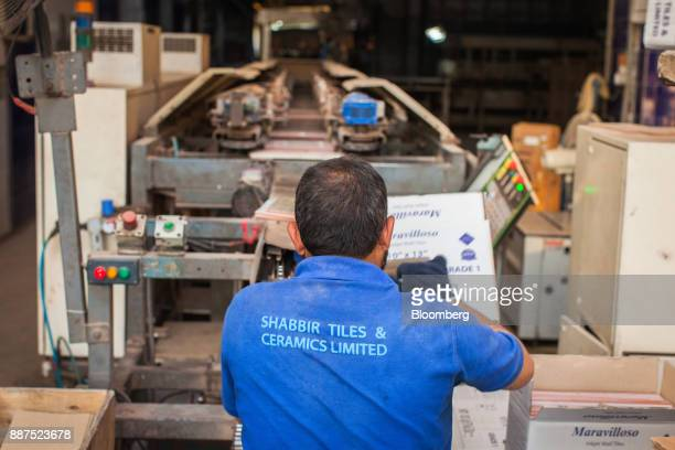An employee packs tiles from a conveyor into a box at the Shabbir Tiles Ceramics Ltd production facility in Karachi Pakistan on Wednesday Dec 6 2017...
