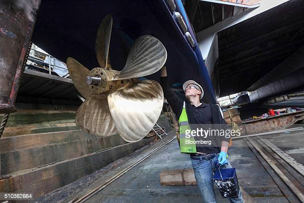 An employee paints the hull of a Thames Clipper catamaran at Turks boatyard in Chatham UK on Thursday Oct 29 2015 The Thames Clipper river bus...
