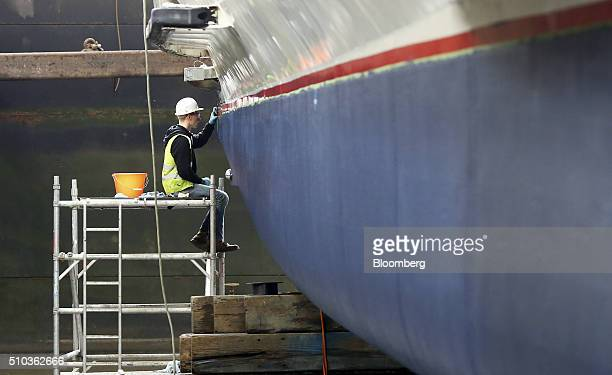 An employee paints the stern of the hull of a Thames Clipper catamaran at Turks boatyard in Chatham UK on Thursday Oct 29 2015 The Thames Clipper...