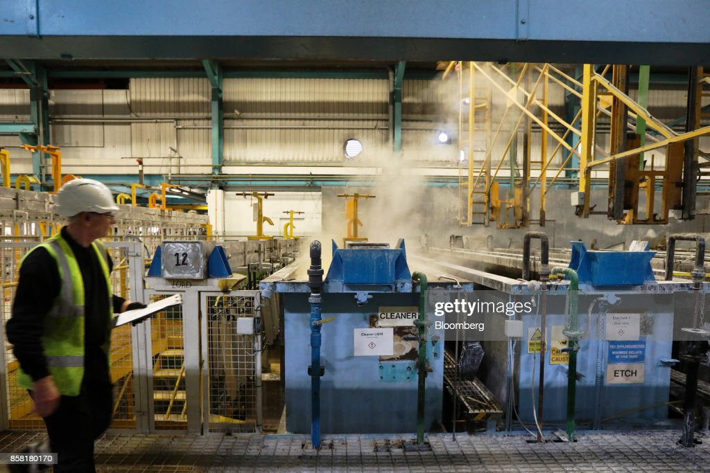 An employee pases steam rising from the cleaning and anodising tanks at the Sapa SA aluminum plant in Bedwas, U.K., on Wednesday, Oct. 4, 2017. After being closed for three years due to a weak market, Sapa's aluminum plant in south Wales reopened to supply lightweight parts for automakers such as London Electric Vehicle Co., the maker of black cabs. Photographer: Luke MacGregor/Bloomberg via Getty Images