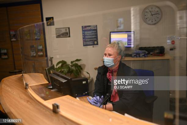 An employee passenger wearing PPE , including a face mask as a precautionary measure against COVID-19, sits behind a perspex safety screen at an...