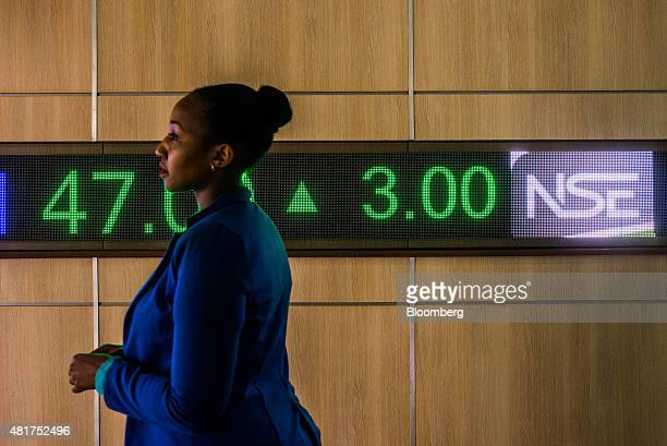 An employee passes a digital ticker showing share prices at the Nairobi Securities Exchange Ltd in Nairobi Kenya on Tuesday July 21 2015 Kenya is a...