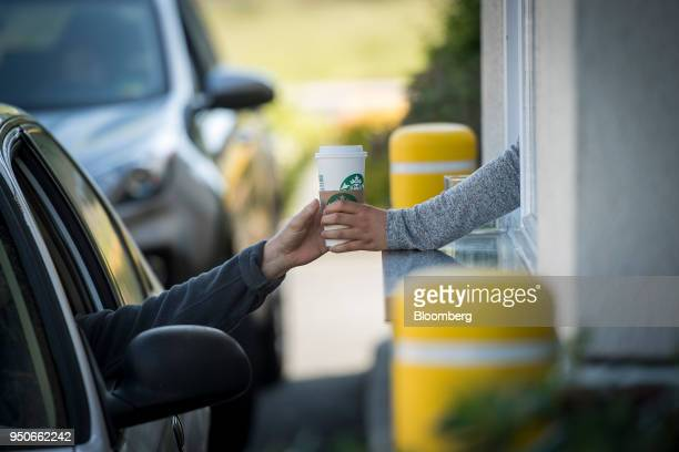 An employee passes a drink order to a customer at the drivethru of a Starbucks Corp coffee shop in Rodeo California US on Monday April 23 2018 The...