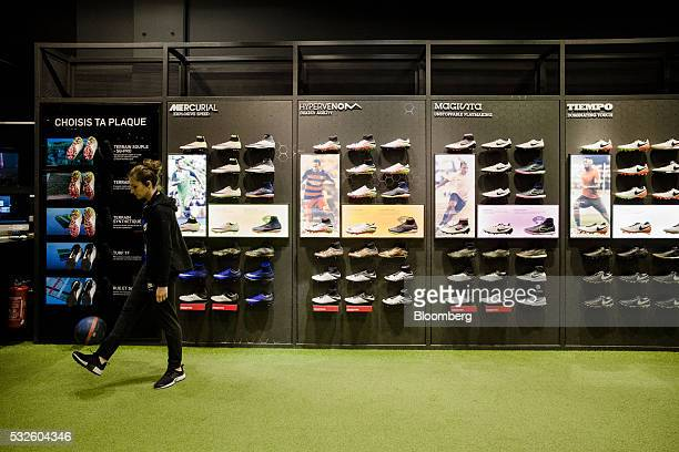 timeless design 8b1f5 63cbd An employee passes a football boot display inside the Nike Inc sports  apparel store in Paris