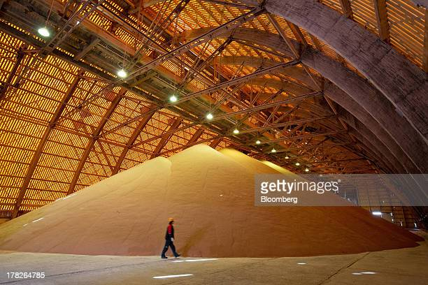 An employee passes a giant pile of potash grain inside a storage facility at the potash mine operated by OAO Uralkali in Berezniki Russia on Monday...