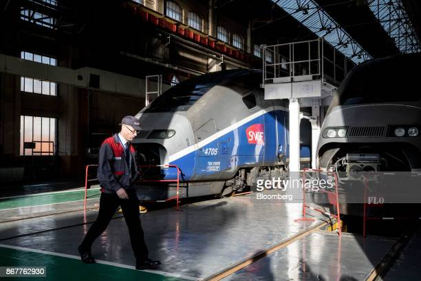 An employee passes a pair of TGV high-speed railway trains inside a hangar at the Alstom SA factory in Belfort, France, on Thursday, Oct. 26, 2017....