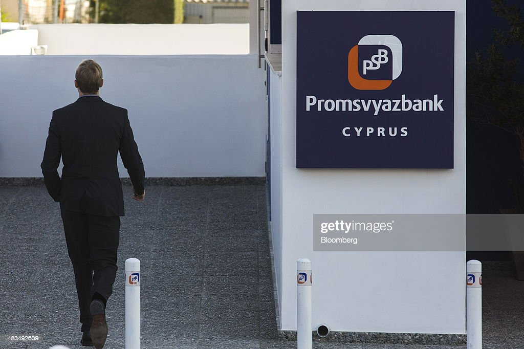 An employee passes a sign outside a Russian OAO Promsvyazbank (PSB) bank branch in Limassol, Cyprus, on Tuesday, April 8, 2014. Cyprus wants to shield financial flows with Russia, where it's the biggest foreign investor, as the U.S. and the European Union ratchet up sanctions in response to President Vladimir Putin's annexing Crimea from Ukraine. Photographer: Andrew Caballero-Reynolds/Bloomberg via Getty Images