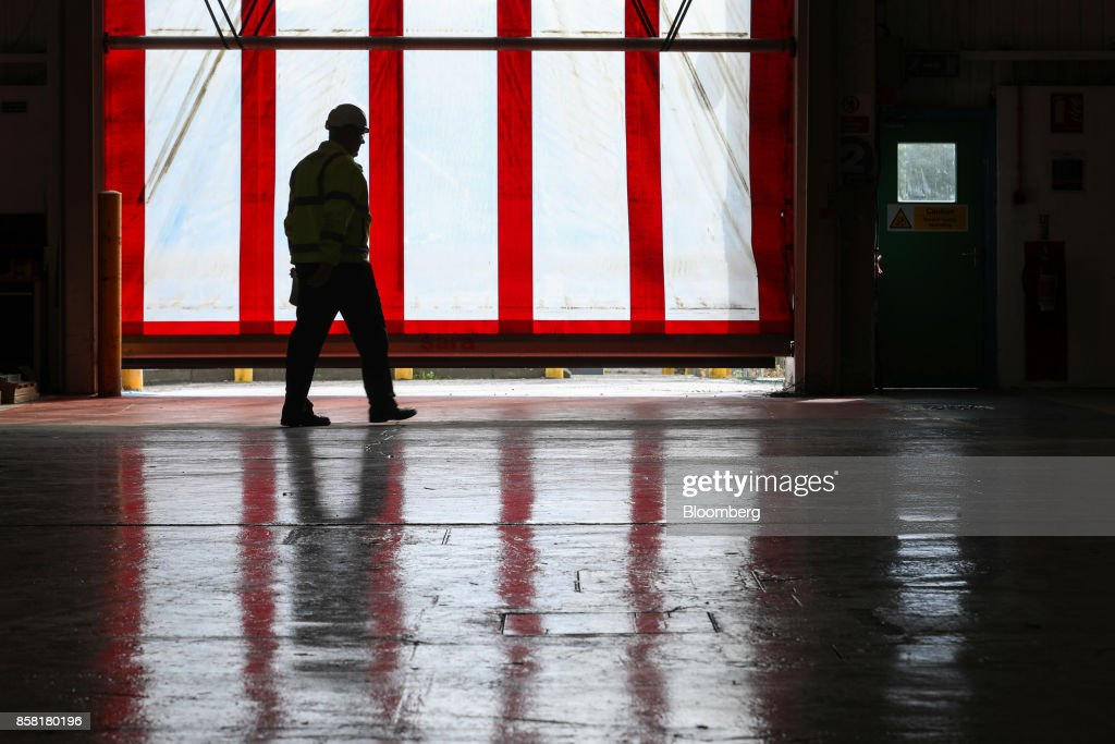 An employee passes an entrance at the Sapa SA aluminum plant in Bedwas, U.K., on Wednesday, Oct. 4, 2017. After being closed for three years due to a weak market, Sapa's aluminum plant in south Wales reopened to supply lightweight parts for automakers such as London Electric Vehicle Co., the maker of black cabs. Photographer: Luke MacGregor/Bloomberg via Getty Images