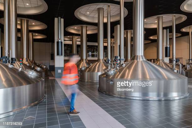 An employee passes beer fermentation tanks in the AnheuserBusch InBev NV brewery in Leuven Belgium on Wednesday July 17 2019 The worlds largest...