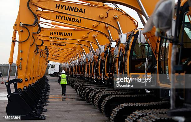 An employee passes beneath a row of Hyundai Robex 145LCR9 excavators at the Port of Tilbury operated by Forth Ports Ltd in Tilbury UK on Tuesday Feb...
