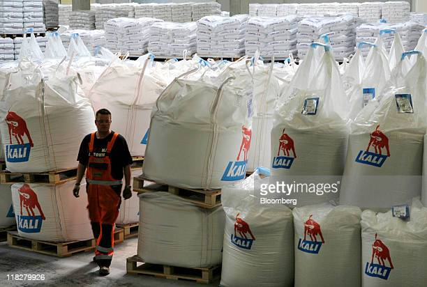 An employee passes KS Kali GmbH branded sacks of potassium chloride also known as potash at the company's warehouse in Bebra Germany on Tuesday July...