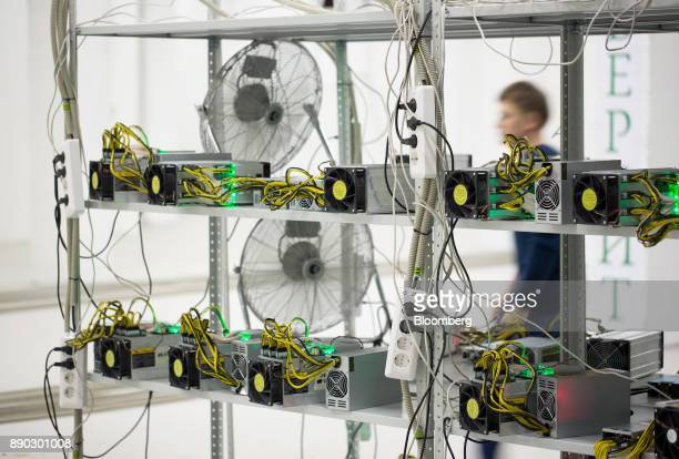An employee passes power supply units and cooling fans linked to cryptocurrency mining machines at the SberBit mining 'hotel' in Moscow Russia on...