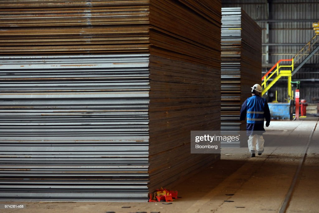 An employee passes stacked sheets of steel in the store room at the SAW Pipe Mills, operated by Liberty Commodities Ltd., in Hartlepool, U.K., on Thursday, June 14, 2018. Steel and aluminumtariffsimposed by the U.S. in March may already be filtering through to prices charged by American producers of the metals. Photographer: Chris Ratcliffe/Bloomberg via Getty Images
