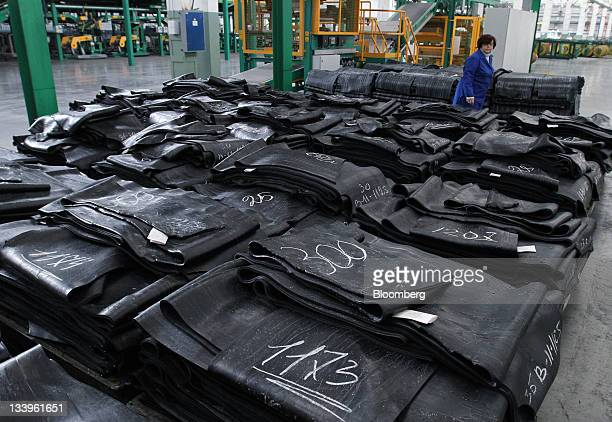 An employee passes strips of rubber, laid out at the ZAO Sibur Holding tire manufacturing plant in Voronezh, Russia, on Friday, Nov. 18, 2011....