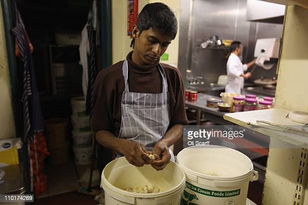 An employee peels garlic in the kitchen of Cafe Bangla curry house on Brick Lane on March 16 2011 in London England From April 2011 the Government...