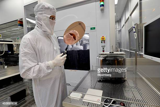 An employee performs a quality control check on an Infineon Technologies AG semiconductor wafer in this arranged photograph in a sterile room at the...