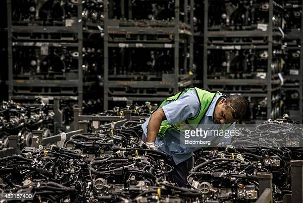 An employee performs a quality control inspection on the assembly line at the Ford Motor Co engine manufacturing facility in Camacari Brazil on...